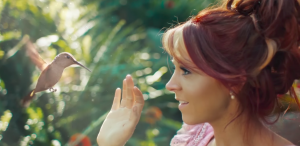 "Lindsey Stirling in her video ""Lost Girls"" looking at a hummingbird"