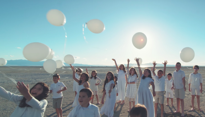 children with roots in Latin America holding balloons in The Prayer music video in English and Spanish