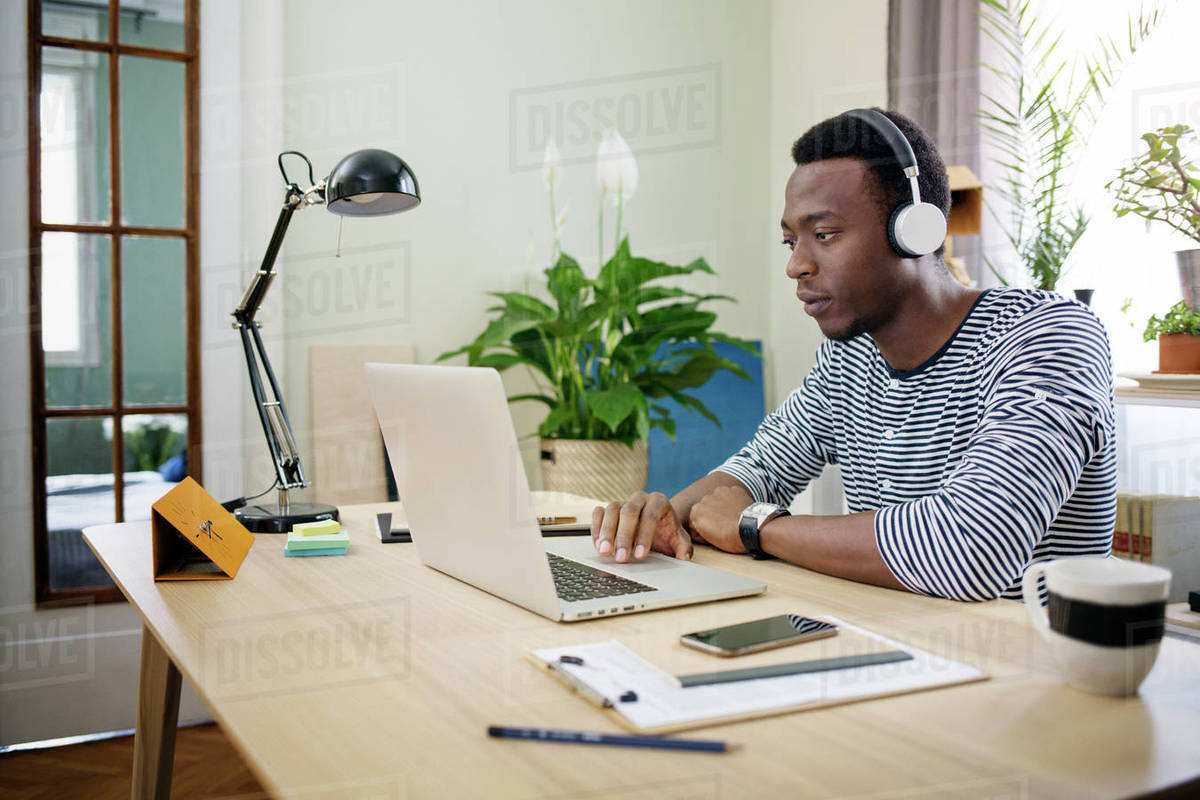 Young man listening to music while working